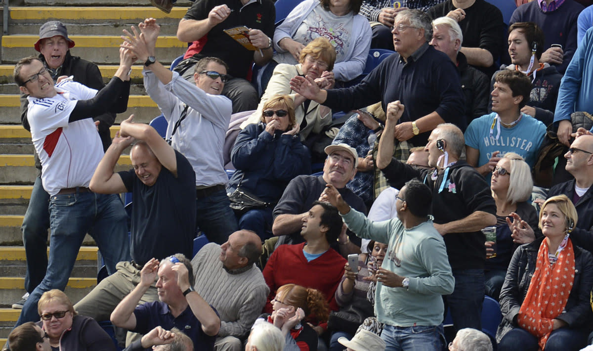 Spectators react as a ball lands in the stand hit for 6 runs by Australia's George Bailey during the fourth one-day international against England at Sophia gardens in Cardiff, Wales September 14, 2013. REUTERS/Philip Brown (BRITAIN - Tags: SPORT CRICKET TPX IMAGES OF THE DAY)