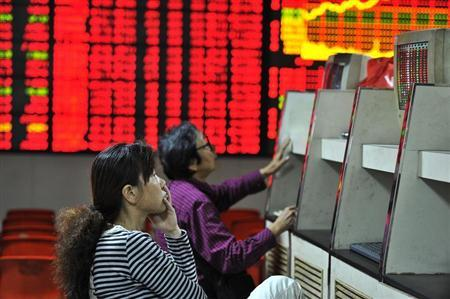 Investors look at computer screens in front of an electronic board showing stock information at a brokerage house in Hefei