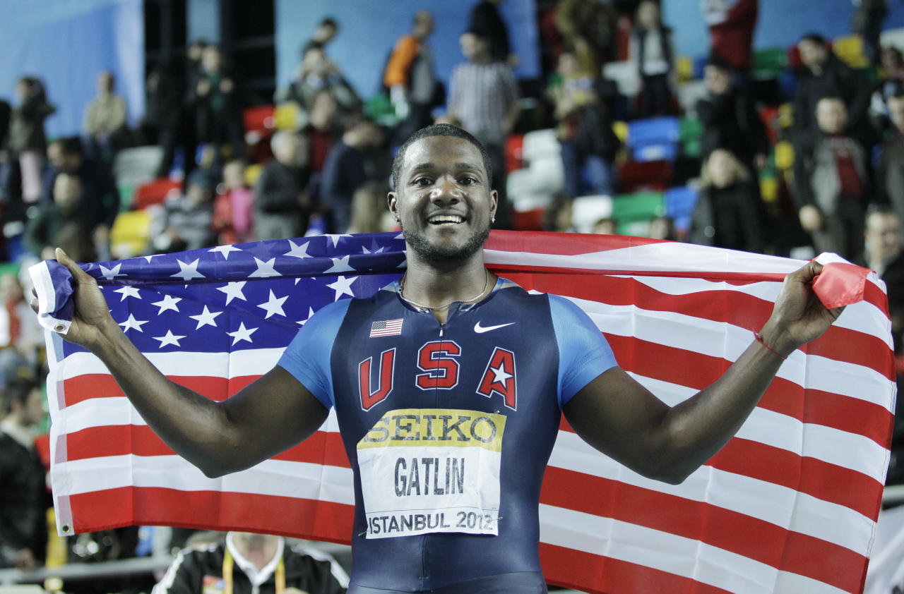 United States' Justin Gatlin celebrates with the American flag after winning the Men's 60m final during the World Indoor Athletics Championships in Istanbul, Turkey, Saturday, March 10, 2012. . (AP Photo/Matt Dunham)