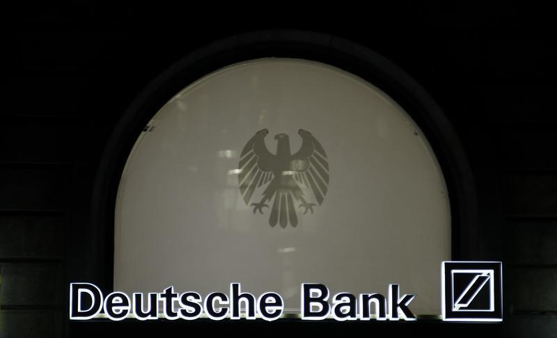 The logo of Germany's largest business bank, Deutsche Bank, is illuminated at the bank's original headquarters in Frankfurt