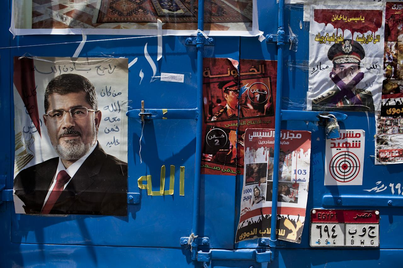 CAIRO, EGYPT - JULY 26: A poster of deposed Egyptian President Mohammed Morsi (L) is dispalyed on a truck beside a poster deriding the Chief of Egypt's Armed Forces, General Abdel Fattah al-Sissi (R), during a demonstration in support of deposed Egyptian President Mohammed Morsi at the Rabaa al-Adweya mosque in the district of Nasr City on July 26, 2013 in Cairo, Egypt. Morsi supporters gathered to protest the overthrow of Morsi, Egypt's first democratically elected leader, by the Egyptian Armed Forces. Muslim Brotherhood leaders called for pro-Morsi protesters to return to the streets on Friday in response to a speech made by General Ahmed Fattah al-Sissi, the Chief of Egypt's Armed Forces, who called for mass anti-Morsi protests across Egypt against 'violence and terrorism' and in support of the military's overthrow of Morsi. (Photo by Ed Giles/Getty Images)