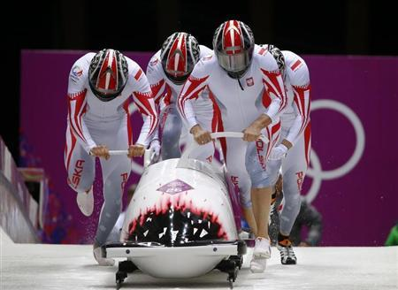 Poland's pilot Kupczyk and his teammates start a heat during the four-man bobsleigh event at the Sochi 2014 Winter Olympics