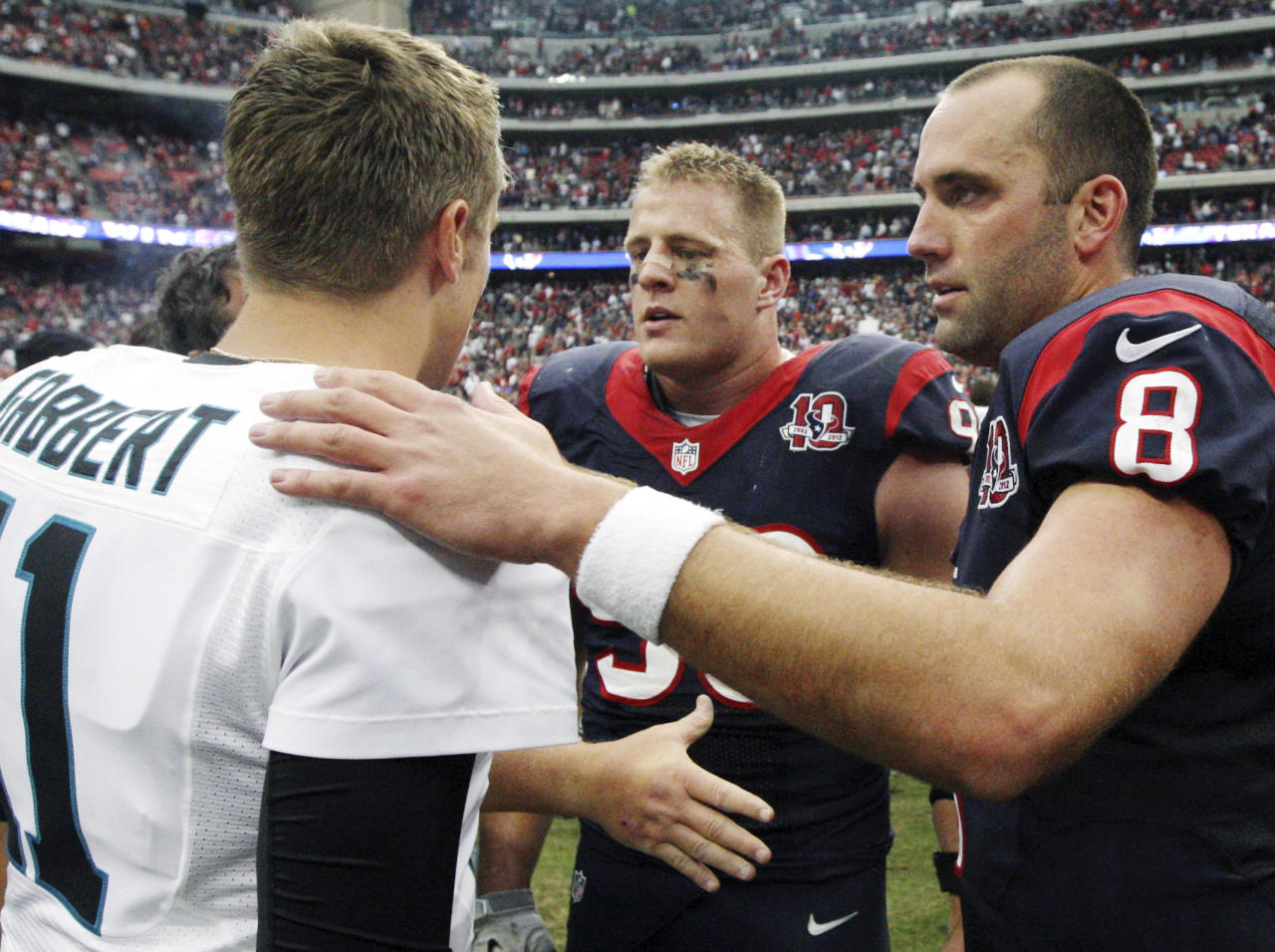 Jacksonville Jaguars quarterback Blaine Gabbert (11) greets Houston Texans quarterback Matt Schaub (8) and J.J. Watt (99) after the Texans defeated the Jaguars 43-37 in overtime of an NFL football game, Sunday, Nov. 18, 2012, in Houston. Gabbert was injured in the first quarter and did not play the rest of the game. (AP Photo/Patric Schneider)