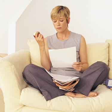 Woman-looking-at-tax-forms-on-sofa-while-eating-apple_web