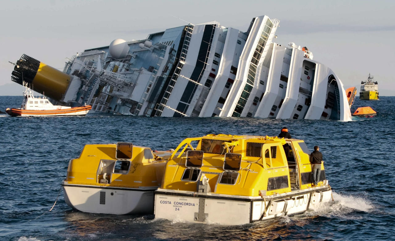 Investigators approach the luxury cruise ship Costa Concordia which leans on its starboard side after running aground in the tiny Tuscan island of Isola del Giglio, Italy, Sunday, Jan. 15, 2012. The Costa Concordia cruise ship ran aground off the coast of Tuscany, sending water pouring in through a 160-foot (50-meter) gash in the hull and forcing the evacuation of some 4,200 people from the listing vessel early Saturday, the Italian coast guard said. (AP Photo/Gregorio Borgia)