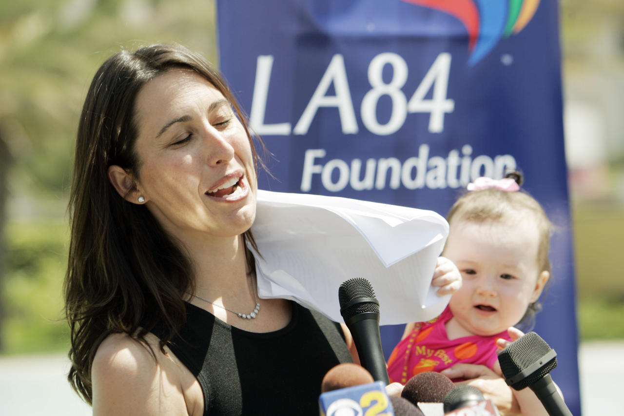 Four-time Olympic gold medalist Janet Evans tries to speak to reporters as her 8-month-old daughter Sydney waves notes around before they take to the pool to promote the LA84 Foundation's 22nd annual Learn-To-Swim program at the John C. Argue Swim Stadium in Exposition Park in Los Angeles on the first day of summer Thursday, June 21, 2007. An offshoot of the 1984  Los Angeles Olympics, the foundation seeks to make swimming lessons available to as many inner city children as possible, particularly ethnic minorities. Studies have shown that African-American and Latino males are more likely to drown than white children in similar age groups. (AP Photo/Reed Saxon)