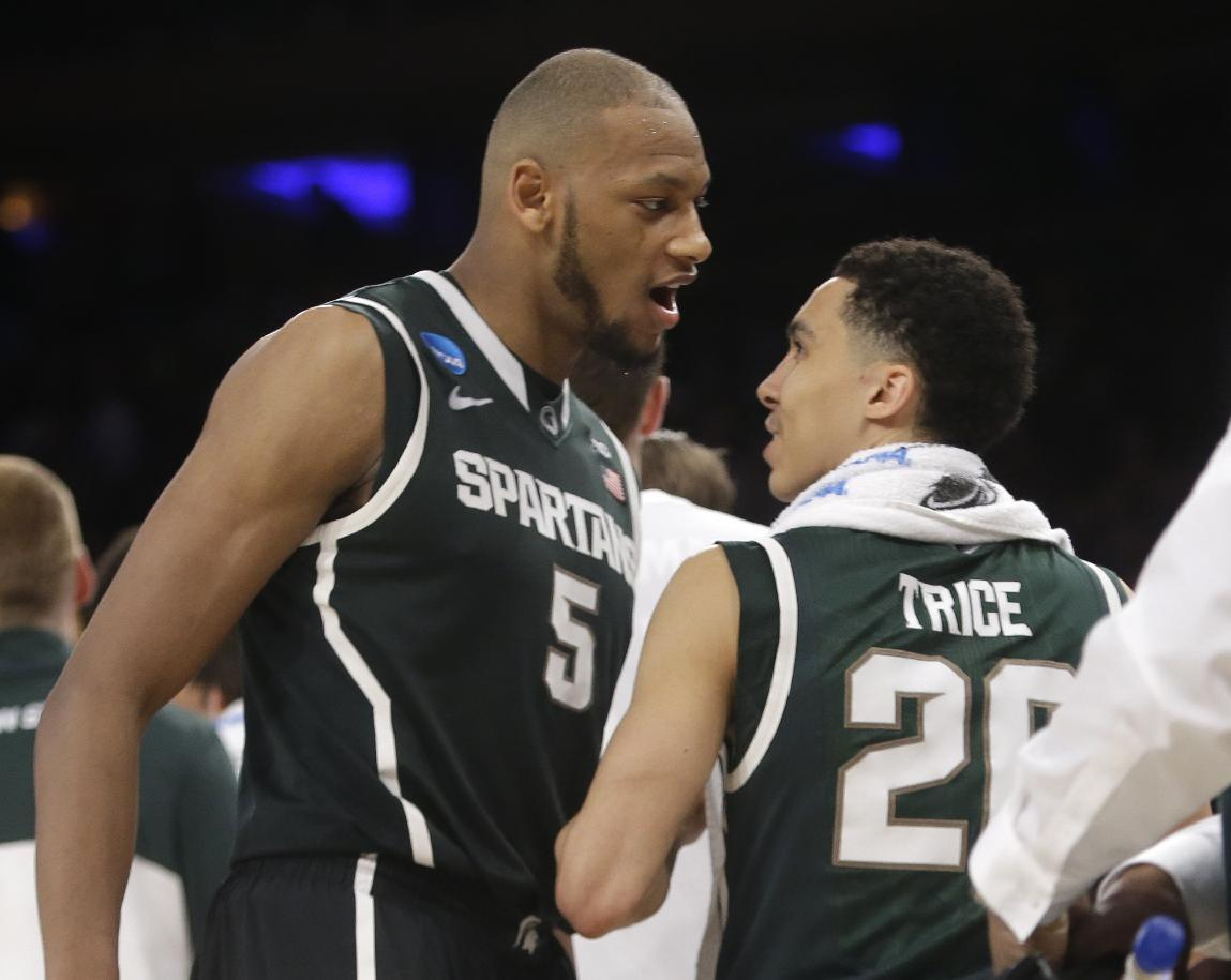 Michigan State's Adreian Payne, left, and Travis Trice celebrate after Michigan State defeated Virginia 61-59 in a regional semifinal of the NCAA men's college basketball tournament, early Saturday, March 29, 2014, in New York. (AP Photo/Frank Franklin II)