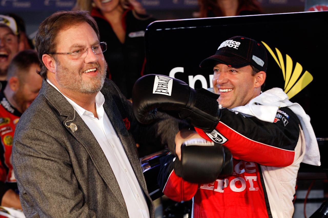 FORT WORTH, TX - NOVEMBER 06:  Texas Motor Speedway president Eddie Gossage (L) poses with Tony Stewart, driver of the #14 Office Depot/Mobil 1 Chevrolet, in Victory Lane after winning the NASCAR Sprint Cup Series AAA Texas 500 at Texas Motor Speedway on November 6, 2011 in Fort Worth, Texas.  (Photo by Chris Graythen/Getty Images)