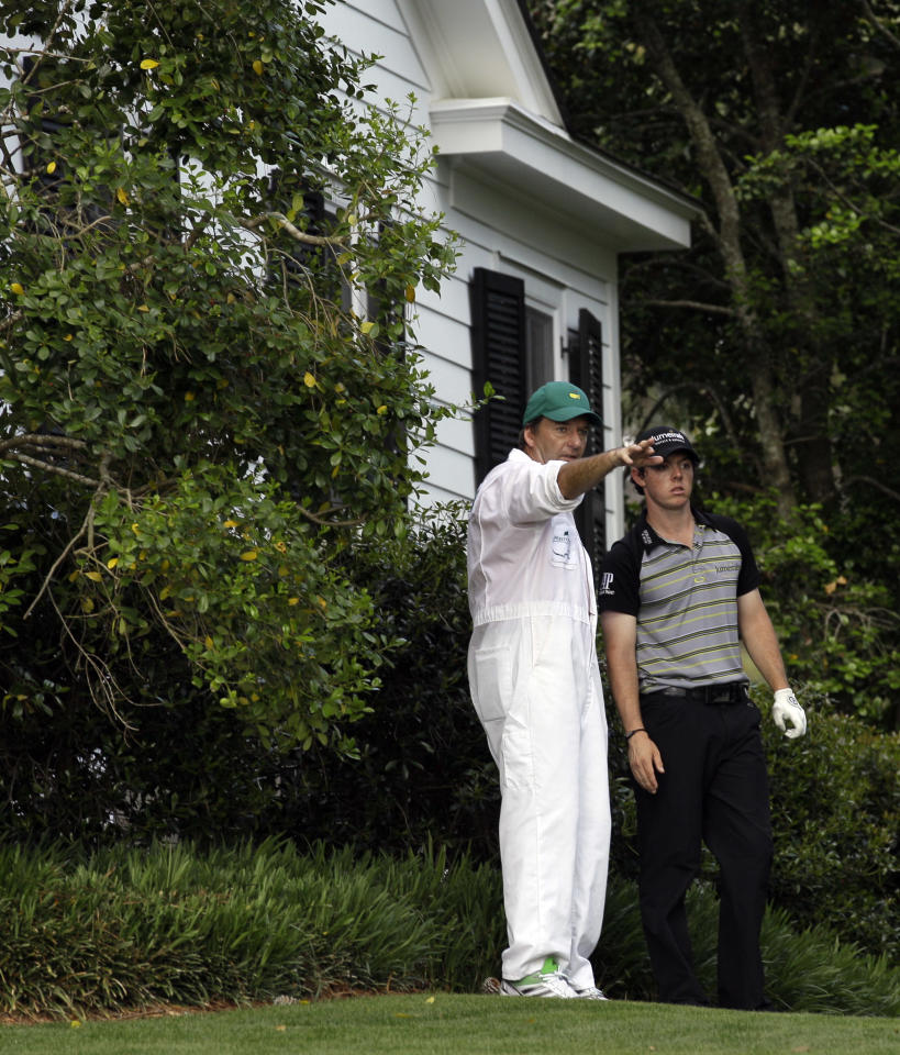 Rory McIlroy of Northern Ireland listens to his caddie J.P. Fitzgerald before hitting his ball out from next to a cabin during the final round of the Masters golf tournament Sunday, April 10, 2011, in Augusta, Ga. McIlroy was playing the 10th hole.