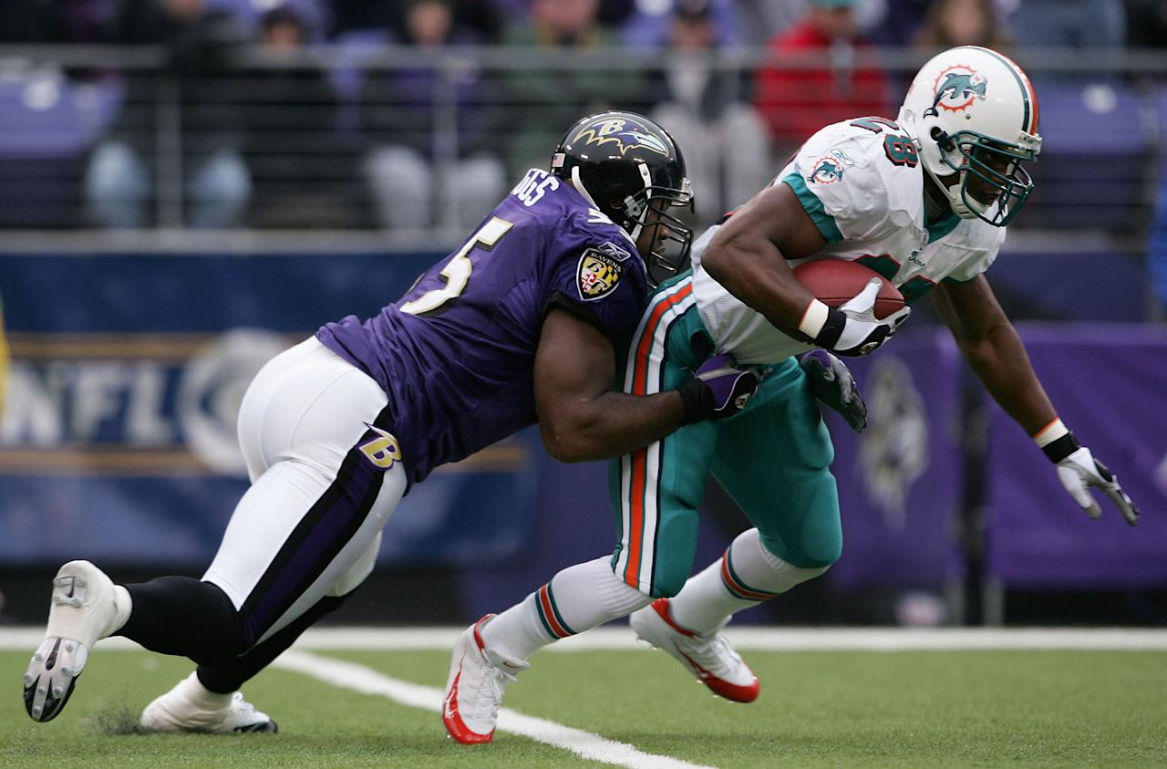 Running back Travis Minor #28 of the Miami Dolphins tries to shake Terrell Suggs #55 of the Baltimore Ravens as the Ravens defeated the Miami Dolphins 30-23 during NFL action at M&T Bank Stadium on January 2, 2005 in Baltimore, Maryland. (Photo by Doug Pensinger/Getty Images)