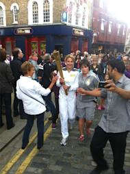 Summer Sanders carries the Olympic torch.