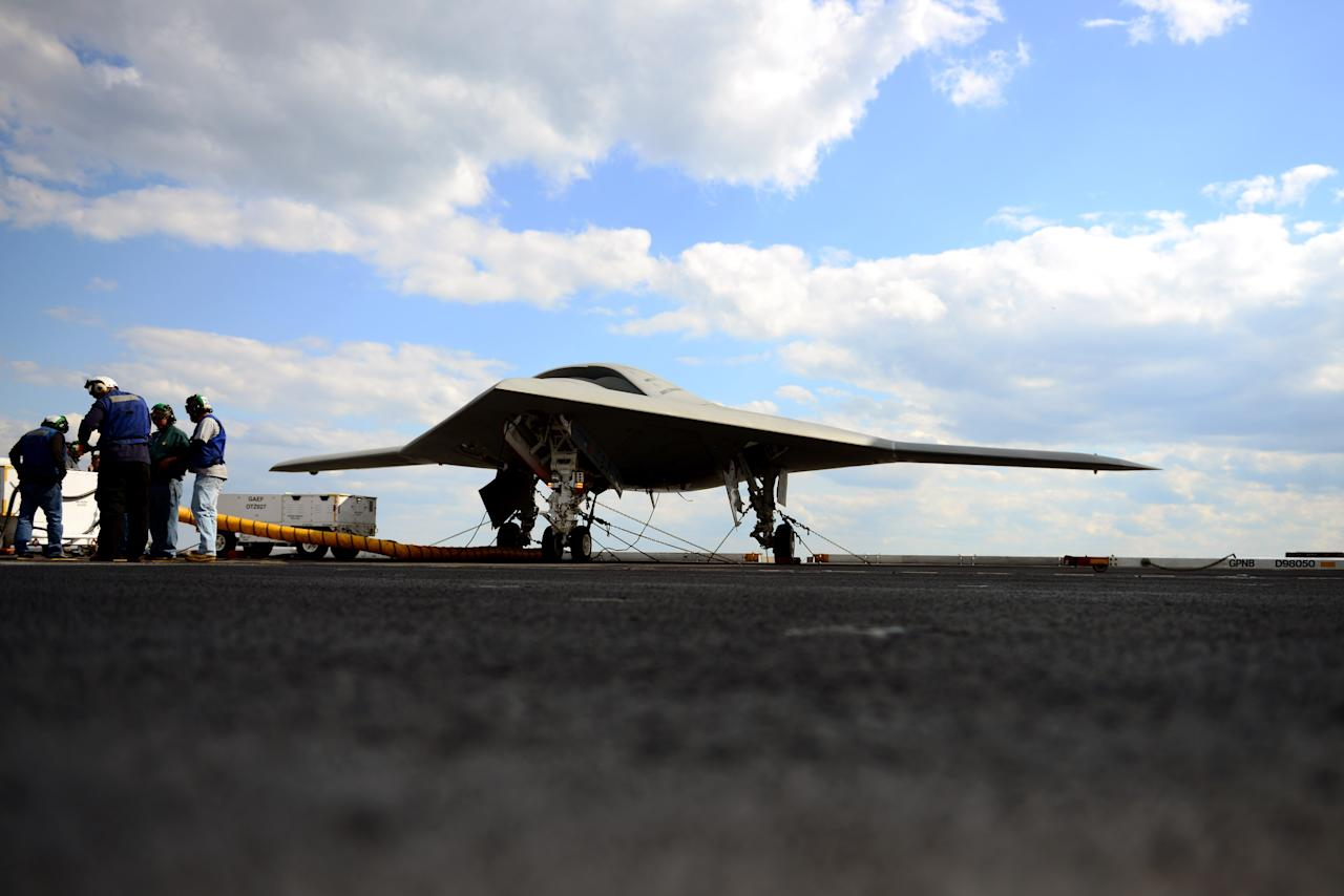 ATLANTIC OCEAN - MAY 13:  In this handout released by the U.S. Navy, Northrop Grumman personnel conduct pre-operational tests on an X-47B Unmanned Combat Air System (UCAS) demonstrator on the flight deck of the aircraft carrier USS George H.W. Bush (CVN 77) May 13, 2013 in the Atlantic Ocean. George H.W. Bush is scheduled to be the first aircraft carrier to catapult-launch an unmanned aircraft from its flight deck. The Navy plans to have unmanned aircraft on each of its carriers to be used for surveillance and be armed and used in combat roles.  (Photo by Mass Communication Specialist 3rd Class Kevin J. Steinberg//U.S. Navy via Getty Images)