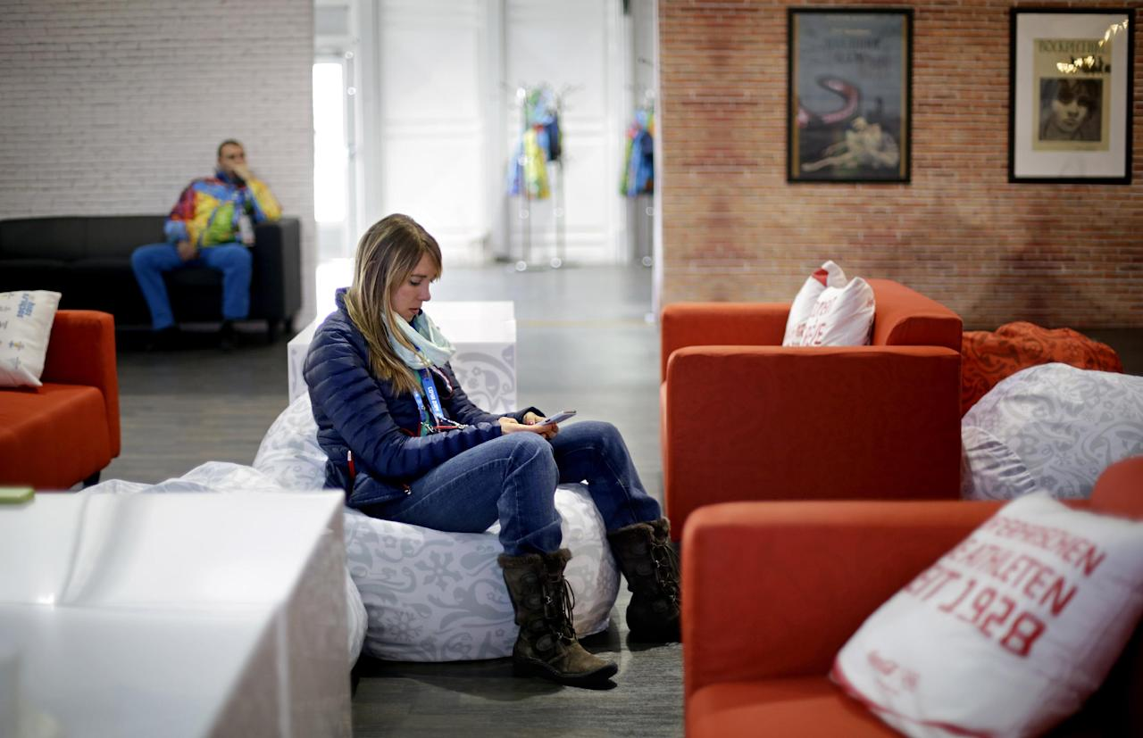 United States speed skater Anna Ringsred uses her mobile phone while sitting in the recreation center of the Coastal Cluster athlete's village at the 2014 Winter Olympics, Tuesday, Feb. 4, 2014, in Sochi, Russia. (AP Photo/David Goldman)