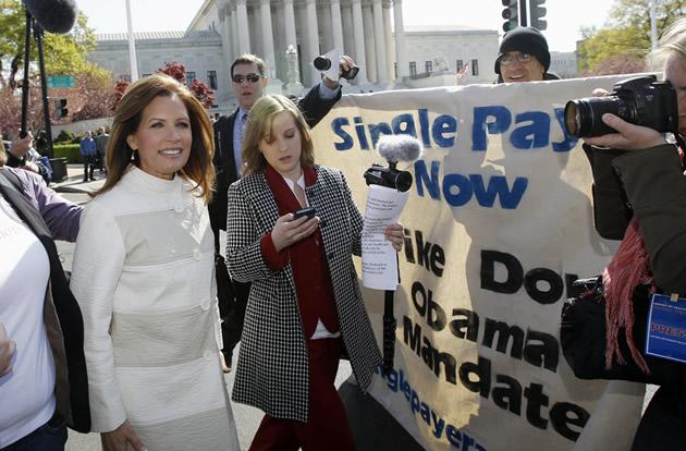 Rep. Michele Bachmann, R-Minn. walks from the Supreme Court, rear, back to the Capitol in Washington, Tuesday, March 27, 2012, after addressing Tea Party supporters and opponents of health care reform.