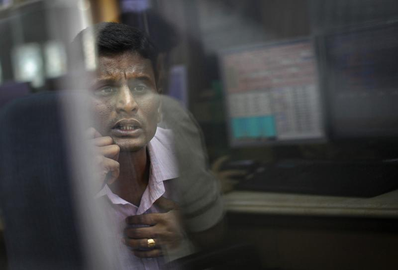 A broker looks at a computer screen as he talks on a phone at a stock brokerage firm in Mumbai