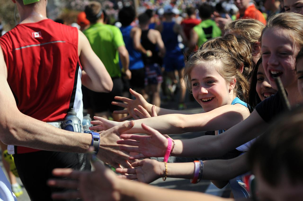 HOPKINTON, MA - APRIL 16: Children slap high fives with passing runners at the start of the 116th running of the Boston Marathon April 16, 2012 in Hopkinton, Massachusetts. (Photo by Darren McCollester/Getty Images)