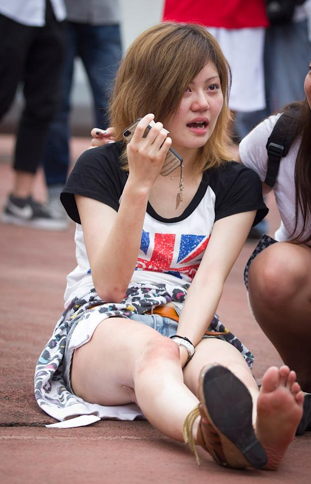 SHANGHAI, CHINA - JUNE 20: (CHINA OUT)  A young woman cries after being caught and hurt in a crush of people as David Beckham arrived at Tongji University on June 20, 2013 in Shanghai, China. The stampede is reported to have left five people injured and hospitalised. (Photo by Getty Images)