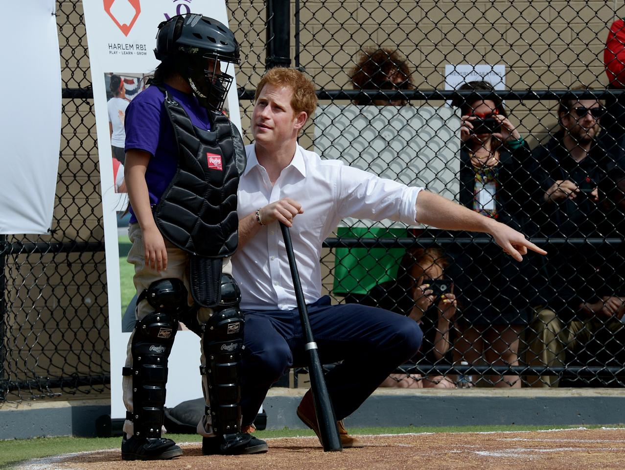NEW YORK, NY - MAY 14:  HRH Prince Harry (R) talks with  a young player while participating in a baseball clinic during the launch of a new partnership between the Royal Foundation of the Duke and Duchess of Cambridge and Harlem RBI, a local community organization May 14, 2013 in the Harlem neighborhood of New York City. HRH will be undertaking engagements on behalf of charities with which the Prince is closely associated on behalf also of HM Government, with a central theme of supporting injured service personnel from the UK and US forces.  (Photo by Justin Lane - Pool/Getty Images)