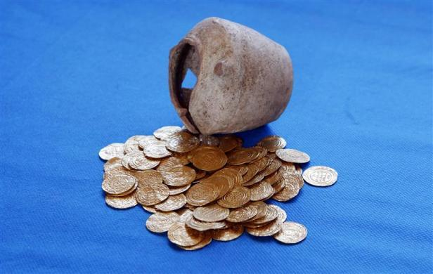 Gold coins and the ceramic jug in which they were found hidden are displayed at the Arsuf cliff-top coastal ruins, 15 km (9 miles) from Tel Aviv, July 9, 2012. The 1,000-year-old hoard of gold coins has been unearthed at the famous Crusader battleground where Christian and Muslim forces once fought for control of the Holy Land, Israeli archaeologists said on July 11, 2012.