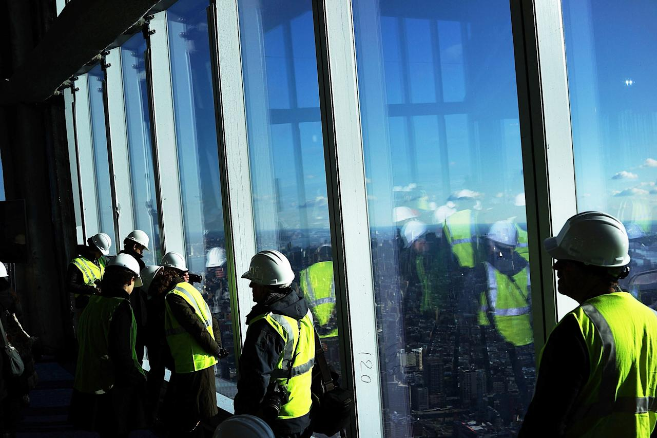 NEW YORK, NY - APRIL 02: Visitors stand near the windows of the One World Observatory from the 100th floor of One World Trade Center at the Ground Zero site on April 2, 2013 in New York City. One World Observatory, which is situated more than 1,250 feet over lower Manhattan, will open to the public in 2015 and will include a pre-show theater, multiple spaces that allow for panoramas of the New York City region and numerous dining options. When completed, One World Trade Center will be the tallest building in the Western Hemisphere at 1776 feet.  (Photo by Spencer Platt/Getty Images)