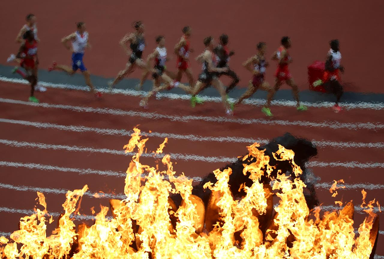 Competitors in the Men's 1500m Semifinal run past the Olympic torch on Day 9 of the London 2012 Olympic Games at the Olympic Stadium on August 5, 2012 in London, England.  (Photo by Jeff J Mitchell/Getty Images)