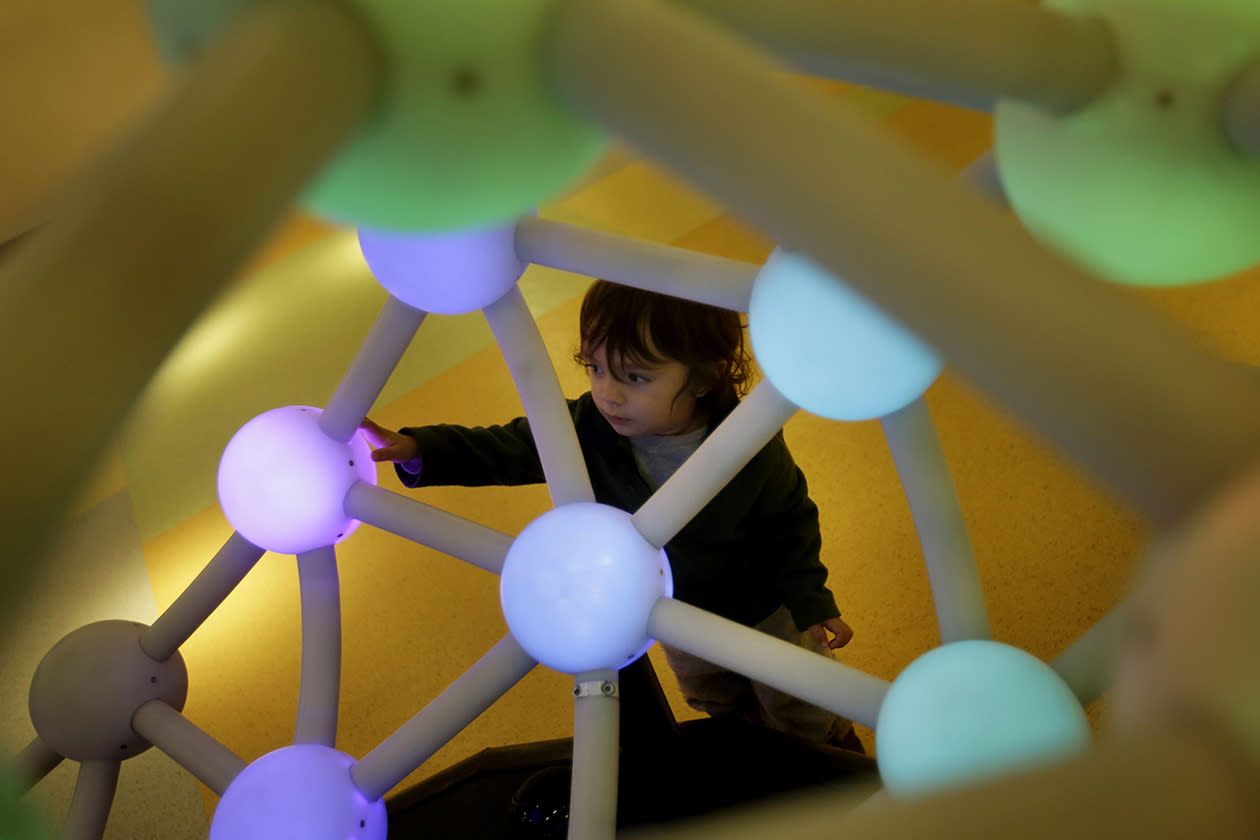Seiji Fankbonner, 1, tries out an interactive display at the new National Museum of Mathematics.