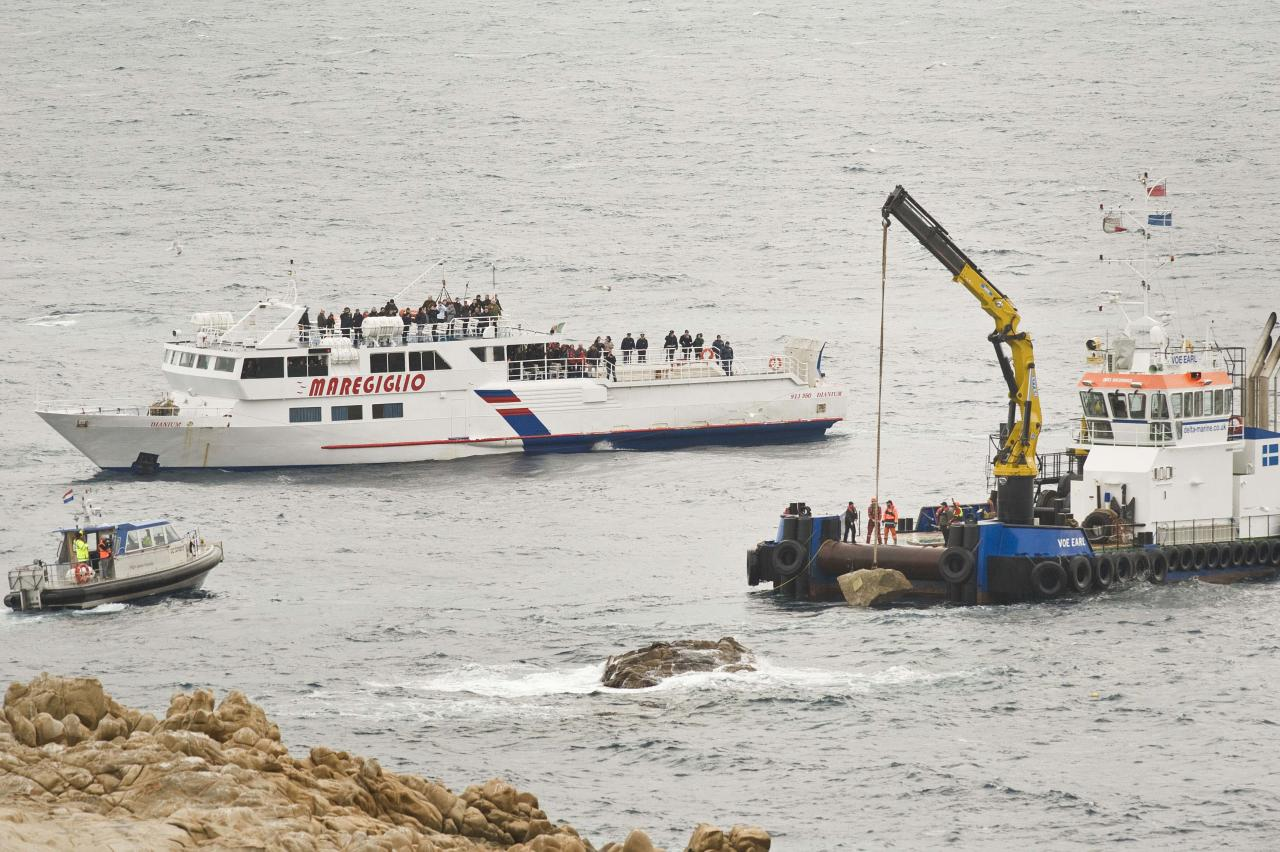 "Workers place part of the ""Le Scole"" rock which was hit by the Costa Concordia cruise ship off the Tuscan Island Isola del Giglio, Italy, Sunday, Jan. 13, 2013. Survivors of the Costa Concordia shipwreck and relatives of the 32 people who died marked the first anniversary of the grounding Sunday. The first event of Sunday's daylong commemoration was the return to the sea of part of the massive rock that tore into the hull of the 112,000-ton ocean liner on Jan. 13, 2012 and remained embedded as the vessel capsized along with its 4,200 passengers and crew. (AP Photo/Antonello Nusca)"
