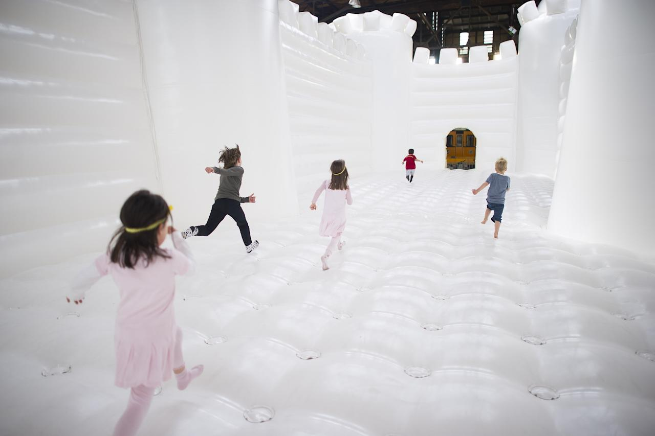 "BERLIN, GERMANY - JUNE 27: Visitors walk in the ""White Bouncy Castle"" of installation artist William Forsythe on June 27, 2013 in Berlin, Germany. The work is a giant, inflatable white castle that Forsythe says encourages people to dance the moment they step into it. ""White Bouncy Castle"" will be open to visitors at Lokhalle Schoeneberg until July 14 and is part of the ""Foreign Affairs"" series of Berliner Festspiele. (Photo by Timur Emek/Getty Images)"