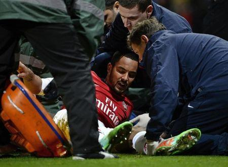 Arsenal's Theo Walcott holds shows his agony as he is injured during their English FA Cup soccer match against Tottenham Hotspur at the Emirates stadium in London