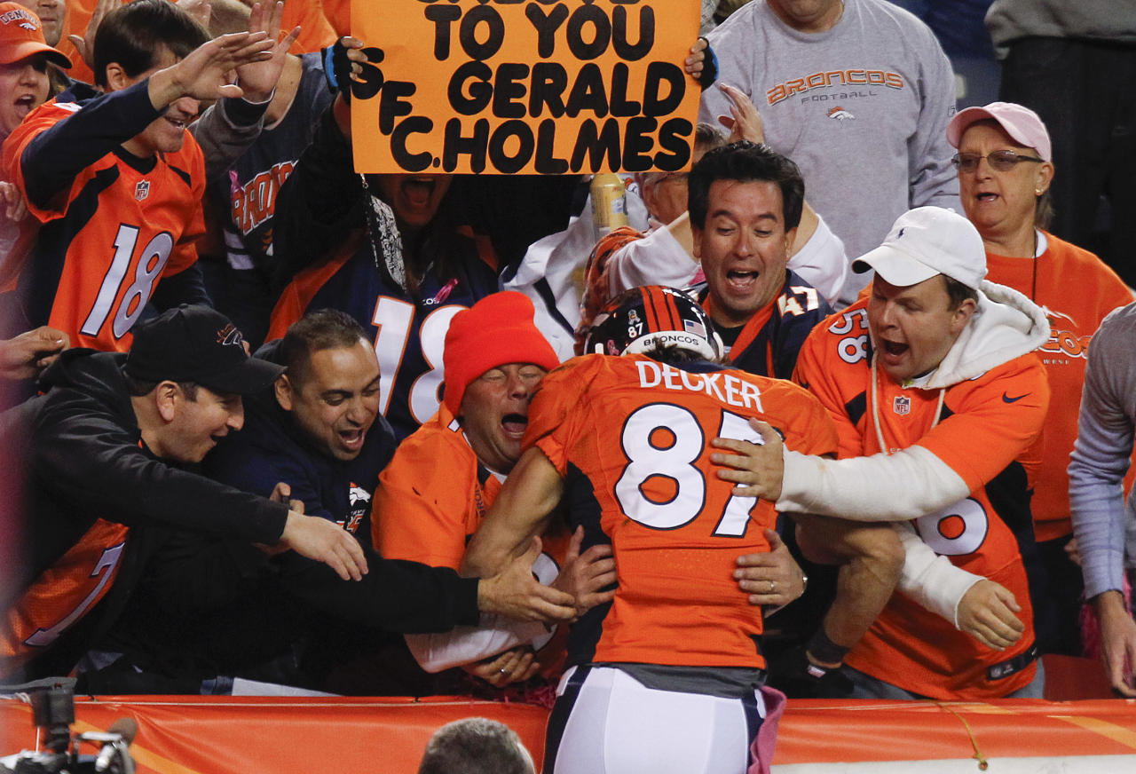 Denver Broncos wide receiver Eric Decker (87) is greeted by fans as he leaps into the stands after scoring a touchdown against the New Orleans Saints in the second quarter of an NFL football game, Sunday, Oct. 28, 2012, in Denver. (AP Photo/David Zalubowski)