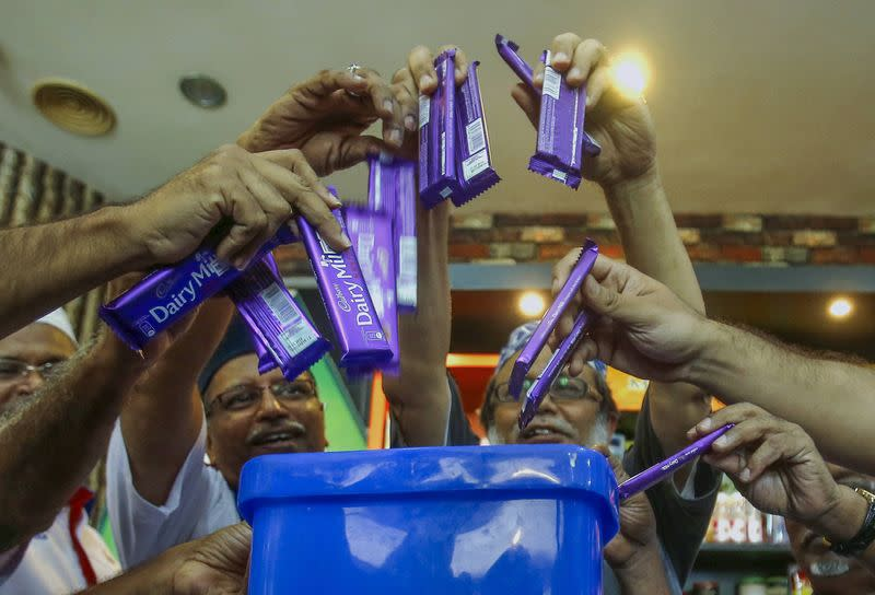 MAWAR members throw Cadbury chocolate products into a dustbin as a protest and officially announced their boycott of Cadbury products, in Kuala Lumpur