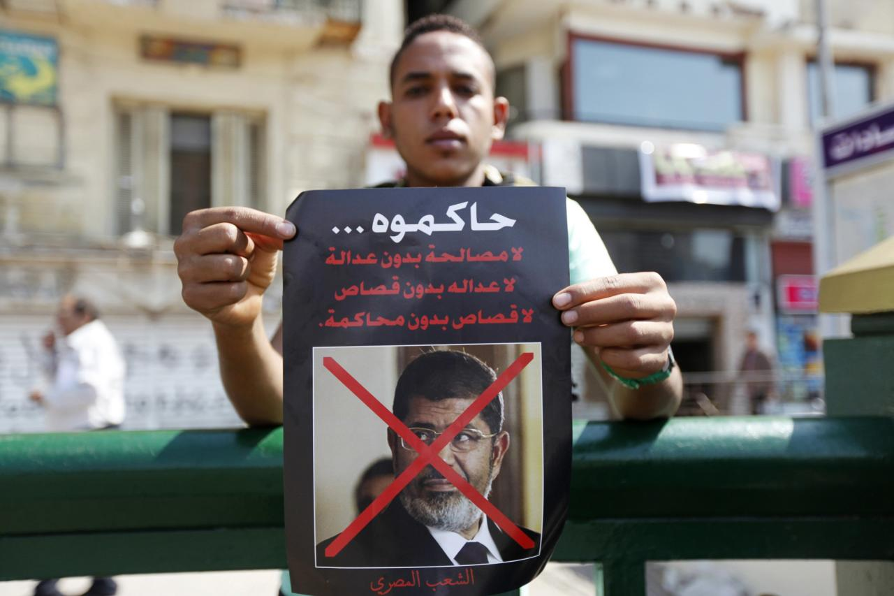 A man carries a poster of ousted Egyptian President Mohamed Mursi, calling for his trial as people gathered to celebrate the anniversary of an attack on Israeli forces during the 1973 war, in Cairo October 6, 2013. REUTERS/Mohamed Abd El Ghany (EGYPT - Tags: POLITICS CIVIL UNREST)