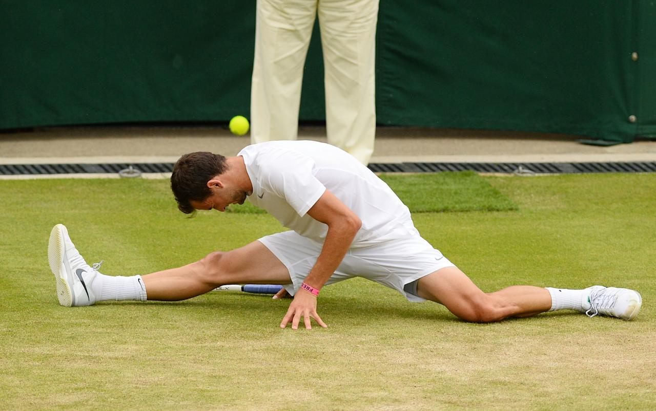 LONDON, ENGLAND - JUNE 27: Grigor Dimitrov of Bulgaria slips on the grass during his Gentlemen's Singles second round match against Grega Zemlja of Slovenia on day four of the Wimbledon Lawn Tennis Championships at the All England Lawn Tennis and Croquet Club on June 27, 2013 in London, England. (Photo by Mike Hewitt/Getty Images)