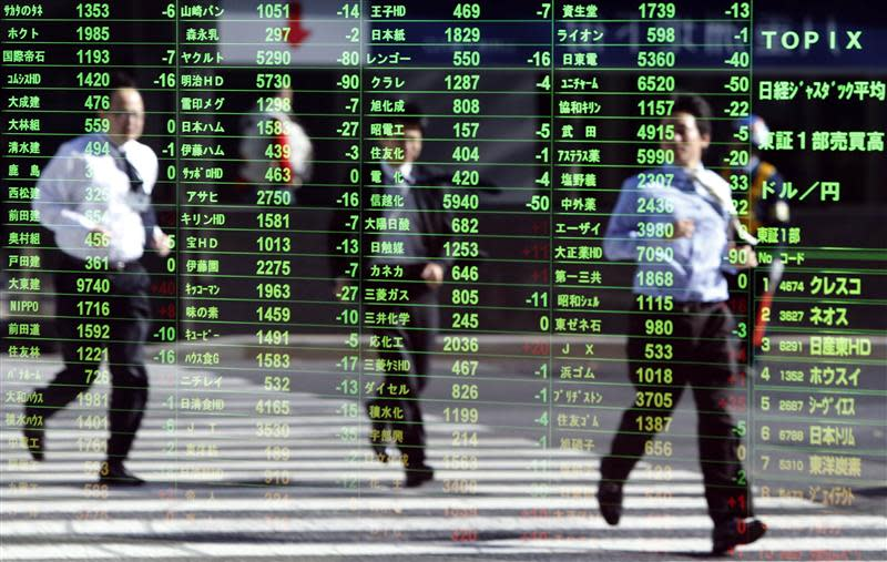 Pedestrians are reflected on a stock quotation board at a brokerage in Tokyo