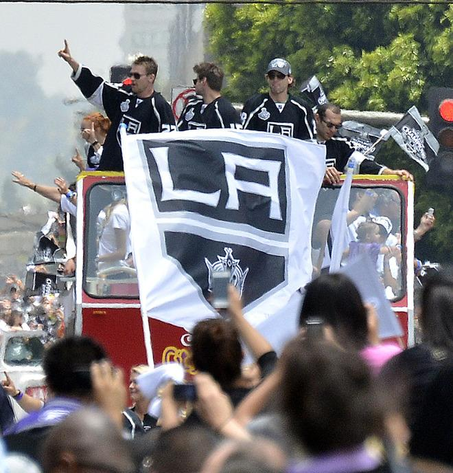 Buses with Los Angeles Kings team members, and their families travel Figueroa Street to the Staples Center during the Stanley Cup victory parade on June 14, 2012 in Los Angeles, California. The Kings are celebrating their first NHL Championship in the team's 45-year-old franchise history.    AFP PHOTO/JOE KLAMARJOE KLAMAR/AFP/GettyImages