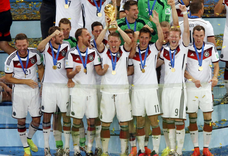 Germany's Bastian Schweinsteiger holds up the trophy as the German team celebrates after winning the World Cup final soccer match between Germany and Argentina at the Maracana Stadium in Rio de Janeiro, Brazil, Sunday, July 13, 2014. Mario Goetze volleyed in the winning goal in extra time to give Germany its fourth World Cup title with a 1-0 victory over Argentina on Sunday