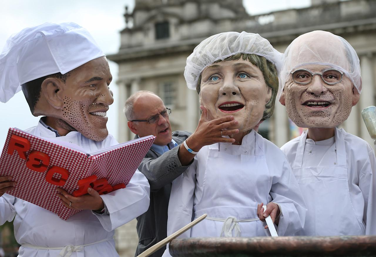 BELFAST, NORTHERN IRELAND - JUNE 16: An Oxfam worker adjusts a mask depicting German Chancellor Angela Merkel as a masks depicting US President Obama (L) and Italian Prime Minister Enrico Letta look on during a photocall on June 16, 2013 in Belfast, Northern Ireland. The G8 group of world leaders will meet tomorrow in Fermanagh, Northern Ireland. (Photo by Peter Macdiarmid/Getty Images)
