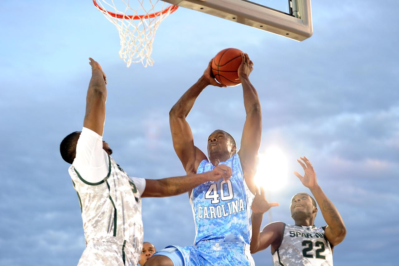 SAN DIEGO, CA - NOVEMBER 11:  Harrison Barnes #40 of the North Carolina Tar Heels goes up for a shot against Derrick Nix #25 and Branden Dawson #22 of the Michigan State Spartans in the first half during the NCAA men's college basketball Carrier Classic aboard the flight deck of the USS Carl Vinson on November 11, 2011 in San Diego, California.  (Photo by Harry How/Getty Images)