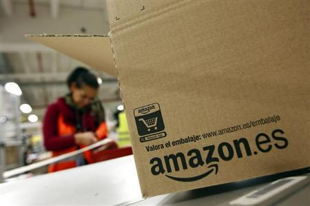 Worker packs box at Amazon's logistics centre in Graben