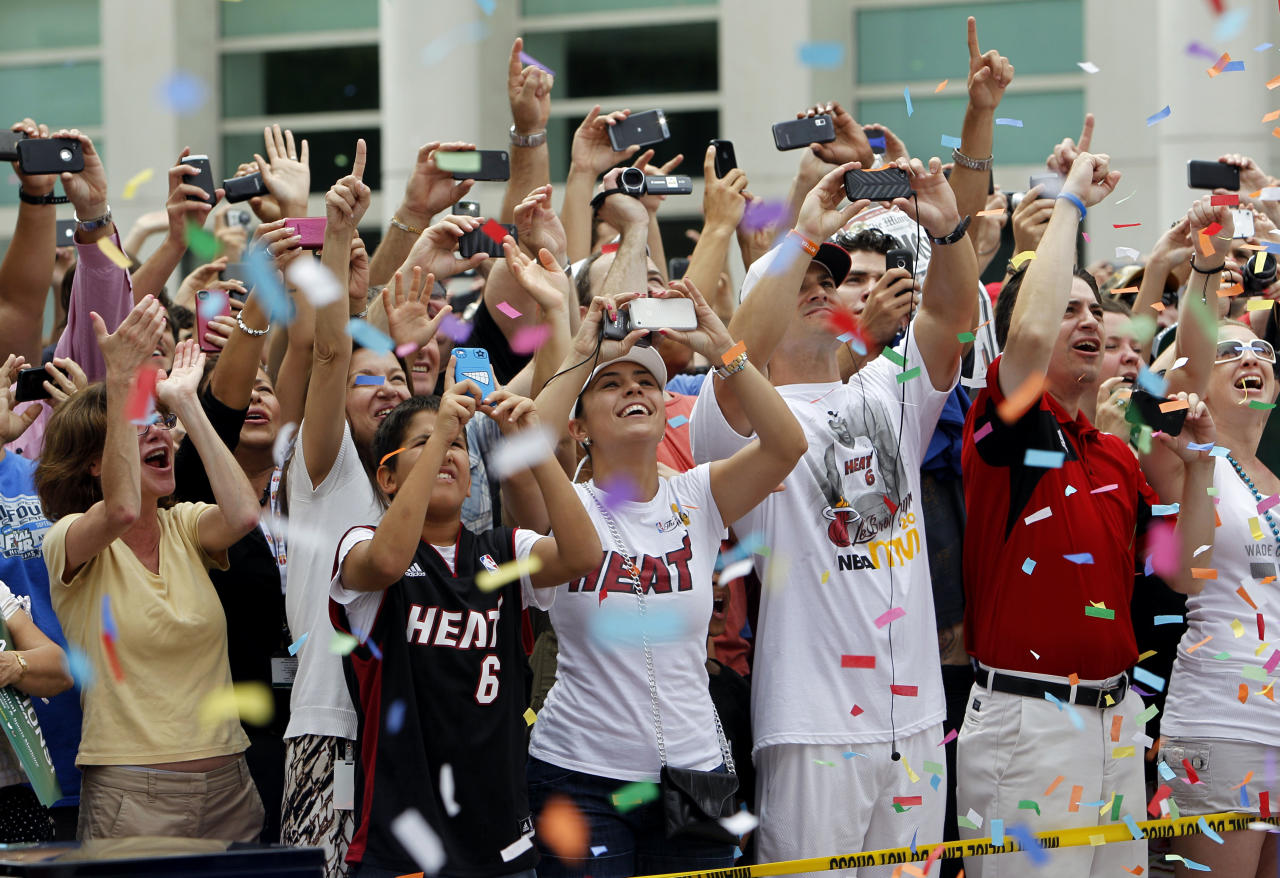 People take photographs as confetti falls on the Miami Heat NBA Finals basketball championship parade Monday, June 25, 2012, in Miami. (AP Photo/Lynne Sladky)