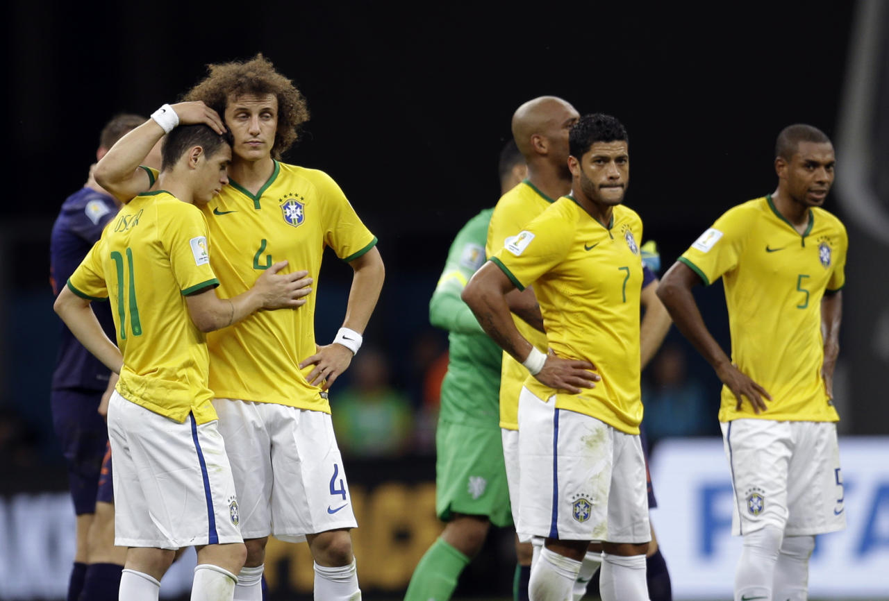 Brazil's David Luiz, left, and Oscar console each other alongside Hulk, center, and Fernandinho, right, after the Netherlands 3-0 victory over Brazil in the World Cup third-place soccer match between Brazil and the Netherlands at the Estadio Nacional in Brasilia, Brazil, Saturday, July 12, 2014. (AP Photo/Natacha Pisarenko)