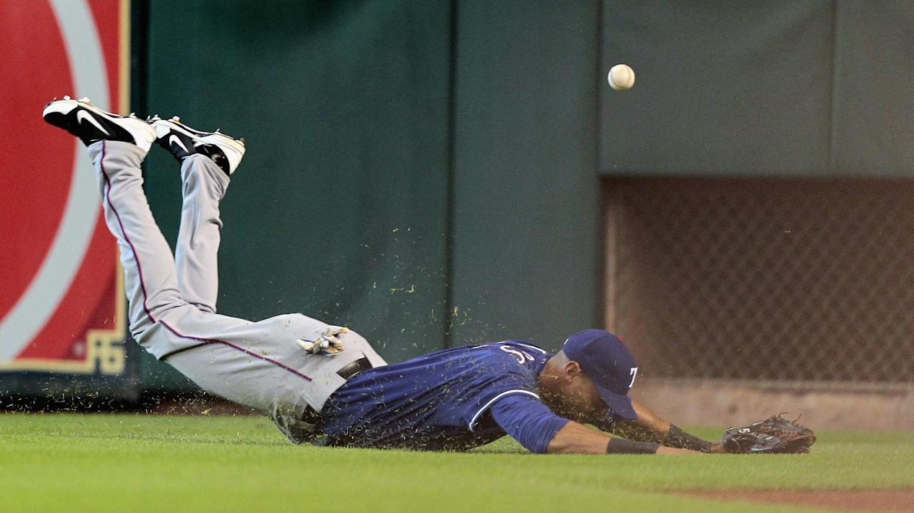 HOUSTON, TX - AUGUST 11: Alex Rios #51 of the Texas Rangers dives but comes up short on a line drive hit by Jose Altuve #27 of the Houston Astros in the first inning at Minute Maid Park on August 11, 2013 in Houston, Texas. (Photo by Bob Levey/Getty Images)