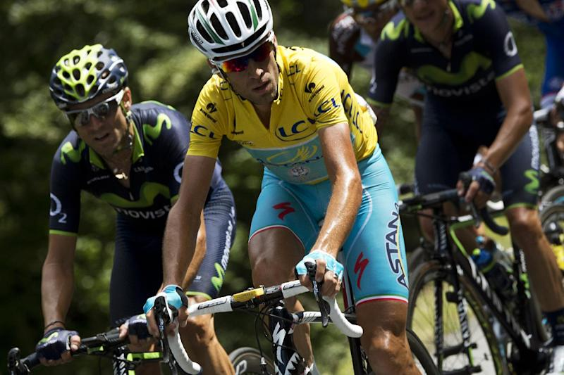 Italy's Vincenzo Nibali (C) wearing the overall leader's yellow jersey, rides in the pack next to Spain's Alejandro Valverde (L) during the 16th stage of the Tour de France between Carcassonne and Bagneres-de-Luchon, southwest France on July 22, 2014