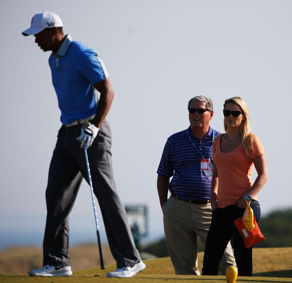 GULLANE, SCOTLAND - JULY 17: Tiger Woods of the United States is watched by Lindsey Vonn and her father Alan Kildow ahead of the 142nd Open Championship at Muirfield on July 17, 2013 in Gullane, Scotland. (Photo by Rob Carr/Getty Images)