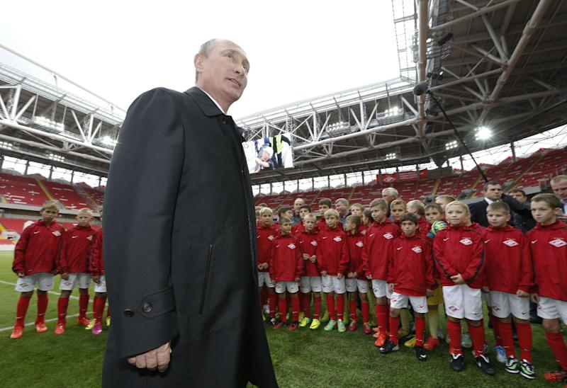 Russian President Vladimir Putin talks to young football players during a visit to Spartak's stadium Otkritye Arena in Moscow, on August 27, 2014