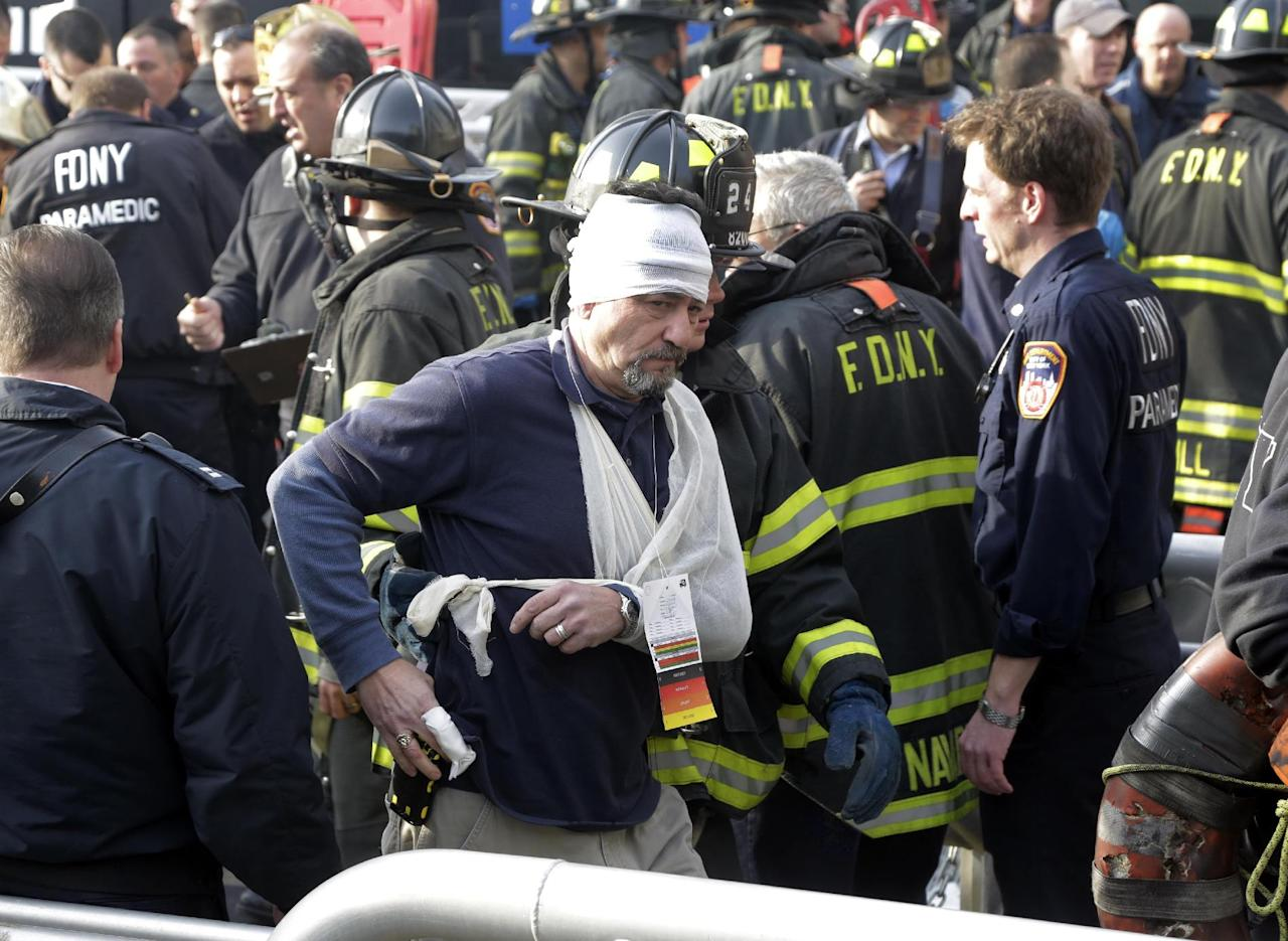 An injured passenger of the Seastreak Wall Street ferry is aided by New York City firefighters, in New York, Wednesday, Jan. 9, 2013. The ferry from Atlantic Highlands, N.J., banged into the mooring as it arrived at South Street in lower Manhattan during morning rush hour, injuring as many as 50 people, at least one critically, officials said. (AP Photo/Richard Drew)