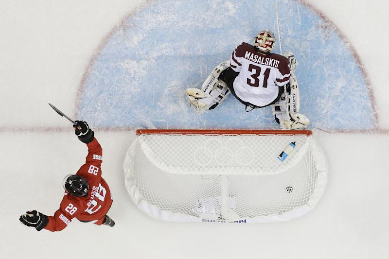 Latvia goaltender Edgars Masalskis looks down at the ice as Switzerland forward Martin Pluss celebrates the winning goal by Switzerland forward Simon Moser during the closing seconds of the 2014 Winter Olympics men's ice hockey game at Shayba Arena, Wednesday, Feb. 12, 2014, in Sochi, Russia