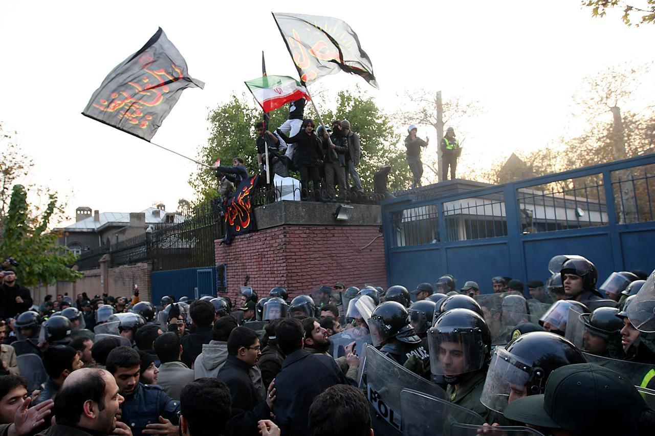 TEHRAN, IRAN - NOVEMBER 29:  A large number of protesters gather in front of riot police and climb a security gate as they prepare to break in to the British Embassy during an anti-British demonstration in the Iranian capital on November 29, 2011 in Tehran, Iran. Relations between the two countries have soured further over recent weeks, with the UK Treasury imposing sanctions on Iranian banks, accusing them of supporting the country's nuclear programme. The Iranian authorities insist that its nuclear plans are for peaceful purposes only and parliament has voted to downgrade diplomatic relations with the UK.  (Photo by FarsNews/Getty Images)