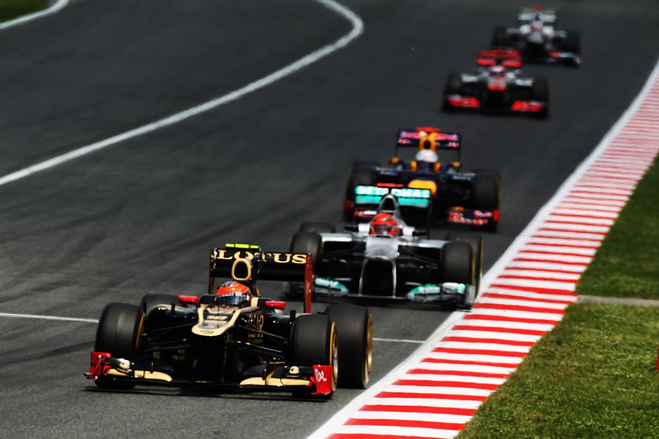 BARCELONA, SPAIN - MAY 13:  Romain Grosjean of France and Lotus heads a train of cars as he drives during the Spanish Formula One Grand Prix at the Circuit de Catalunya on May 13, 2012 in Barcelona, Spain.  (Photo by Mark Thompson/Getty Images)