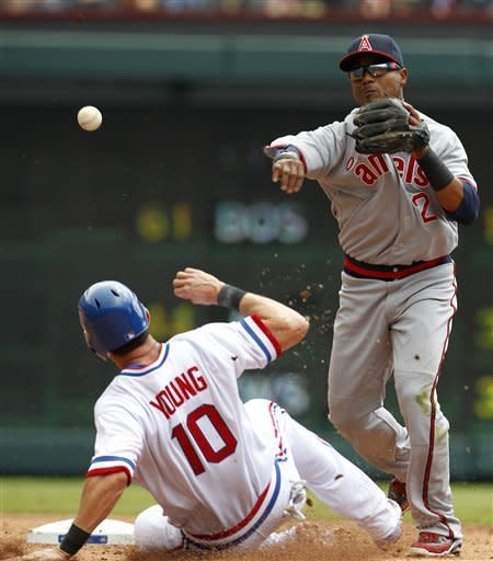 Los Angeles Angels shortstop Erick Aybar (2) makes the throw to first for the double play after getting the force on Texas Rangers' Michael Young (10) in the second inning of a baseball game Saturday, May 12, 2012, in Arlington, Texas. The Rangers Nelson Cruz was out at first. (AP Photo/Tony Gutierrez)